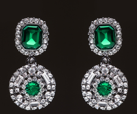 earrings with green stones on the black background