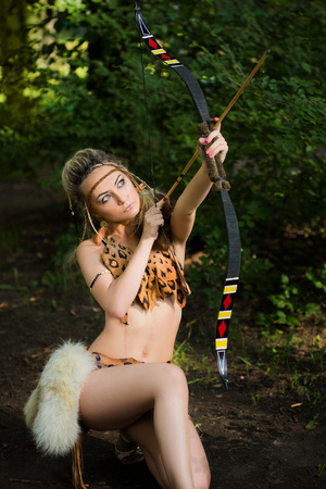 active arrow: Beautiful amazon woman posing with bow in green forest Stock Photo