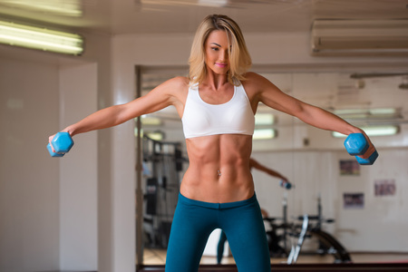 athletic body: young beautiful girl engaged in fitness with dumbbells in the gym