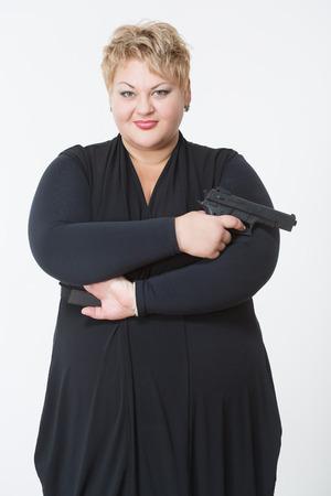 mujer fea: mujer gorda con un arma. en un vestido negro sobre un fondo claro Foto de archivo