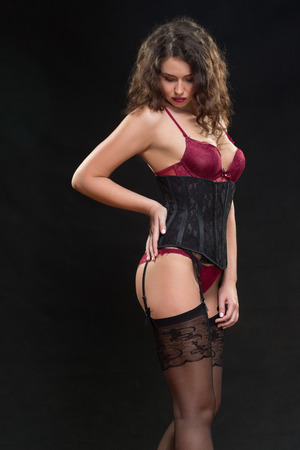 sexy breasts: fashion photo of sexy brunet curly woman in lace lingerie and stockings with a belt posing at studio