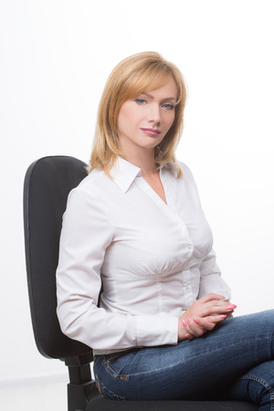 corporate women: Beautiful adult  business woman sitting on a chair. Isolated on white.