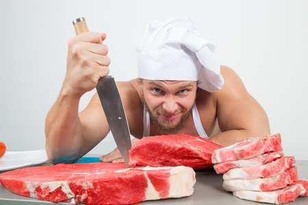 muscular man: close-up of chef in a nightcap with huge pieces of meat on the table. bodybuilder