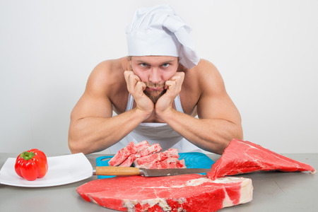 nightcap: close-up of chef in a nightcap with huge pieces of meat on the table. bodybuilder