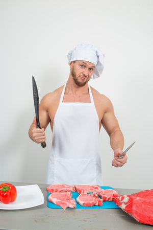 bodybuilder man holding a piece of raw meat. on a white background