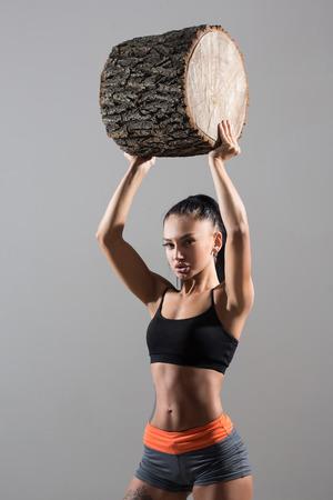 holding aloft: muscular woman holding aloft a log. Muscular female body with sweat. Perfect sportive female body. Stock Photo