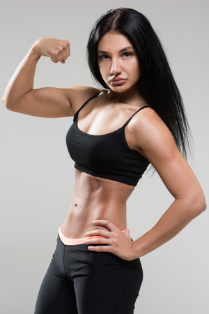 muscular body: Portrait of young fitness woman shows biceps. Muscular female body with sweat. Perfect sportive female body. Stock Photo