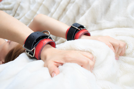 sex toys: female hands in leather handcuffs. on the background sheet. sex toys. passion