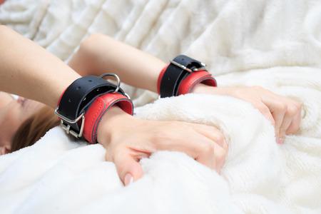 Weibliche Hände in Lederhandschellen. auf dem Hintergrund Blatt. Sex-Spielzeug. Leidenschaft Standard-Bild - 45605164