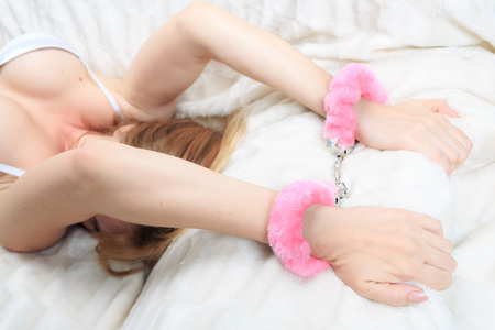 female hands in pink fur handcuffs. on the background sheet. sex toys. passion Stock Photo