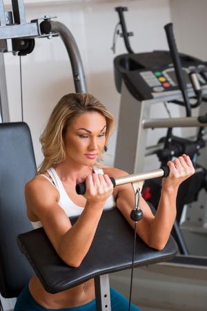simulator: Beautiful girl in sports club on simulator. training biceps