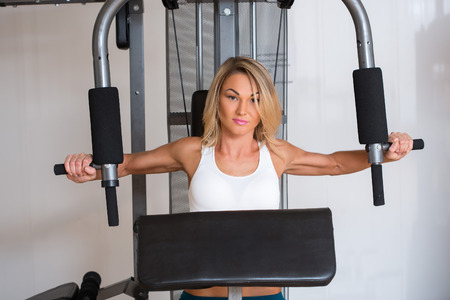pectoral: Beautiful girl in sports club on simulator. Training pectoral muscles