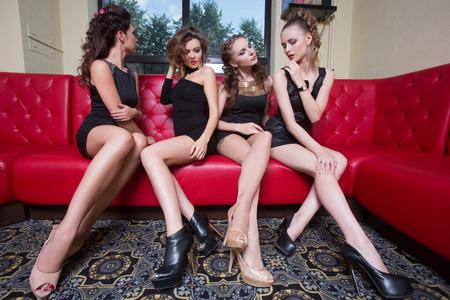 junge nackte m�dchen: Vier reizvolles M�dchen im schwarzen kurzen Kleid auf einer roten Couch. im Innern