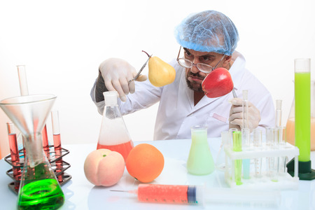 scientist fills chemicals fruit and vegetables. chemistry