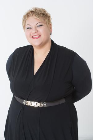 mujer gorda: Sonriente mujer de grasa en vestido negro. fondo claro Foto de archivo