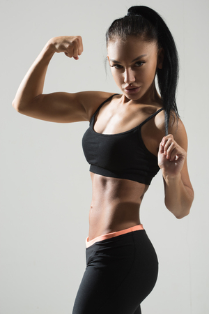 cuerpo femenino perfecto: Portrait of young fitness woman shows biceps. Muscular female body with sweat. Perfect sportive female body. Foto de archivo