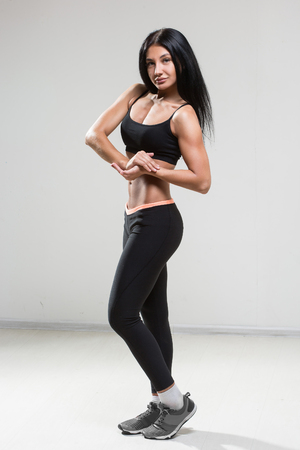 brawny: Portrait of young fitness woman shows biceps. Muscular female body with sweat. Perfect sportive female body. Stock Photo