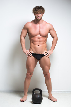 nipple man: Sexy bodybuilder against a white wall.  kettlebell. full height