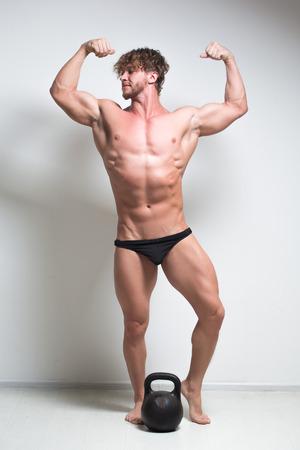 full height: Sexy bodybuilder against a white wall.  kettlebell. full height