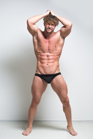nipple young: Sexy bodybuilder against a white wall. full height