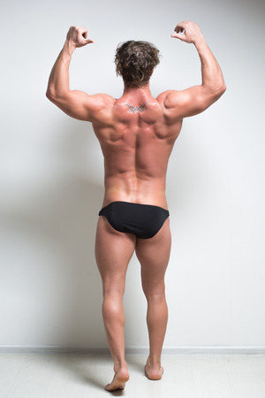 full height: Sexy bodybuilder against a white wall. is back.  full height
