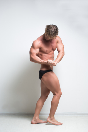 full height: Sexy bodybuilder against a white wall. full height