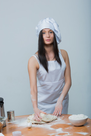 knead: sexy  woman in chef uniform knead the dough on white background