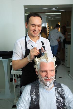 repaint: man repaint the hair in a beauty salon. hair coloring