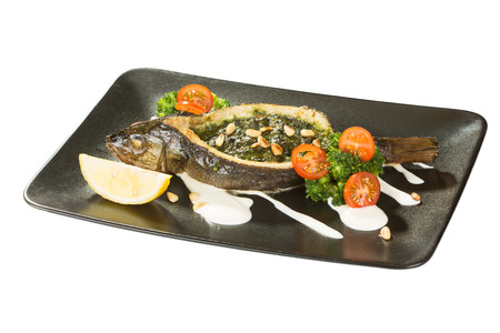 seafood: Stuffed seabass on a black plate with a lemon