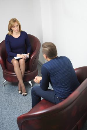 psicologia: Psic�logo Mujer consultar hombre pensativo durante la sesi�n de terapia psicol�gica Foto de archivo