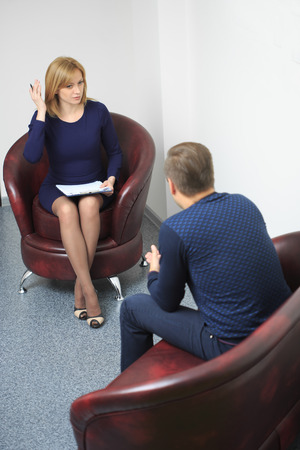 psychology: Female psychologist consulting pensive man during psychological therapy session