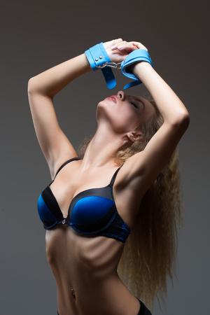 секс: Женщина в нижнем белье, кусать наручники, секс игры Фото со стока