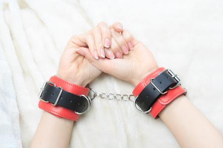 seks: vrouwelijke handen in lederen handboeien. op de achtergrond vel. seksspeeltjes. passie