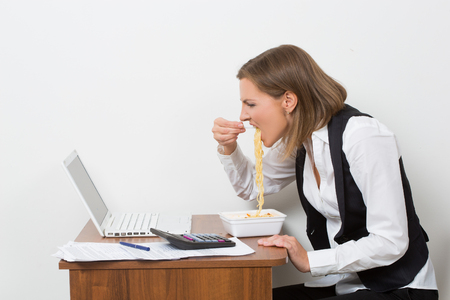 office time: The girl eats a pasta, working behind the laptop. Stock Photo