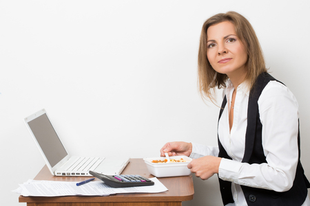 eats: The girl eats a pasta, working behind the laptop. Stock Photo