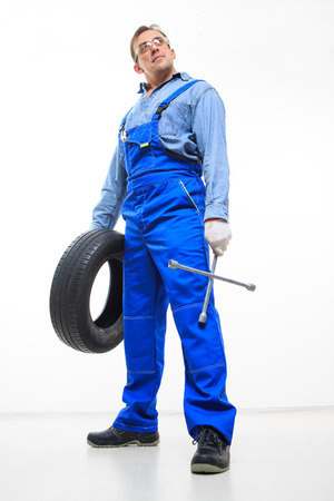 adult male: adult male mechanic with a wrench and tire in the goggles Archivio Fotografico