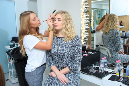 esthetician: make up artist doing professional make up of young woman Stock Photo