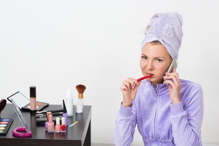 oral communication: beautiful woman brushing her teeth and talking on the phone Stock Photo