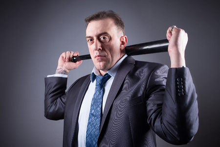 gangster background: male gangster with baseball bat on a gray background
