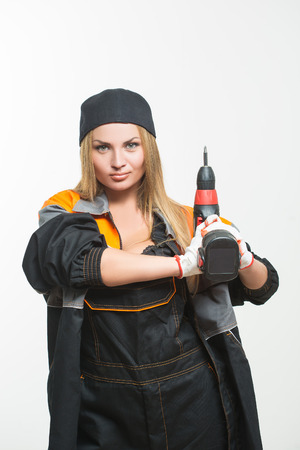 sexy boobs: Young sexy female holding a cordless screwdriver. white isolated background Stock Photo