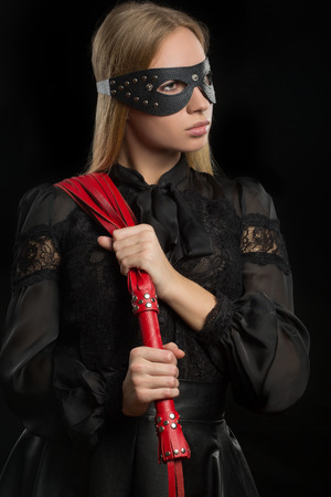 sadistic: portrait of a girl with red leather whip and mask BDSM