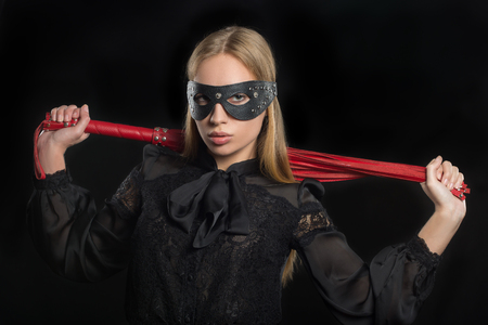 bdsm: portrait of a girl with red leather whip and mask BDSM