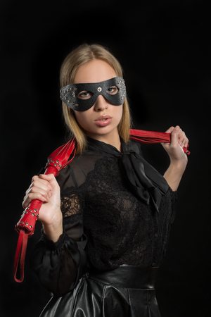 fetishism: portrait of a girl with red leather whip and mask BDSM