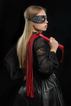portrait of a girl with red leather whip and mask BDSM