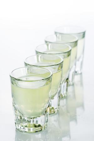 shooter drink: Beautiful shot glasses back lit on white background