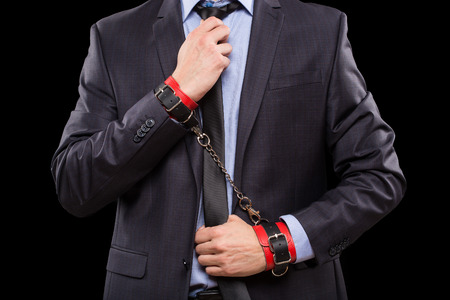 sex toys: a man in a business suit with leather bound with handcuffs. sex Toys