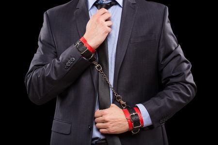 sexo: un hombre en un traje de negocios con cuero atado con esposas. Juguetes sexuales