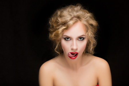 irony: woman model with beautiful makeup and hairstyle shows tongue Stock Photo