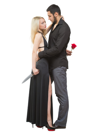 traitor: girl holding a knife traitor. man with a rose in his hand. on a white background Stock Photo