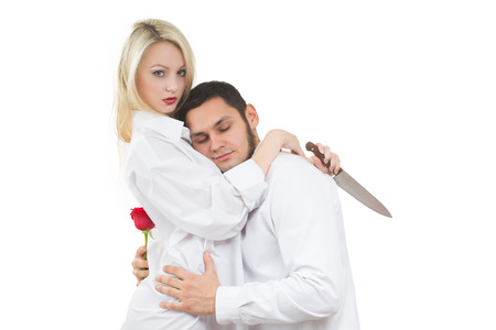 holding a knife: girl holding a knife traitor. man with a rose in his hand. on a white background Stock Photo
